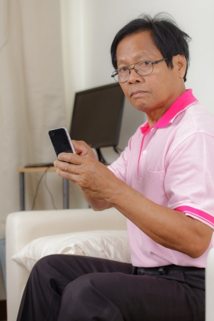 Portrait of Senior man using phone at home photo