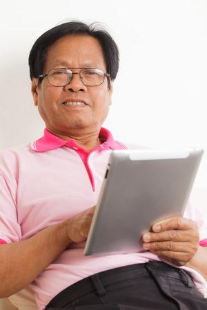 Senior man using digital tablet at home photo