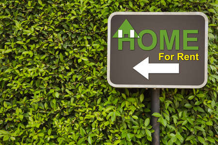 Home for rent sign on green leaves wall photo