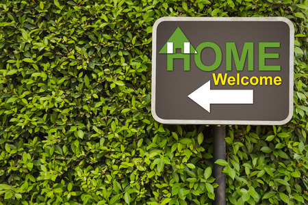 Home welcome sign on green leaves wall photo