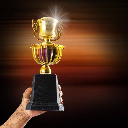 award trophy: Hand holding golden trophy