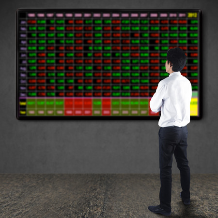 Businessman looking at TV screen with Market analyzing, Business charts and markets on display photo