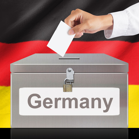 elector: Hand with ballot and metal box with Germany flag, elections and democracy concept