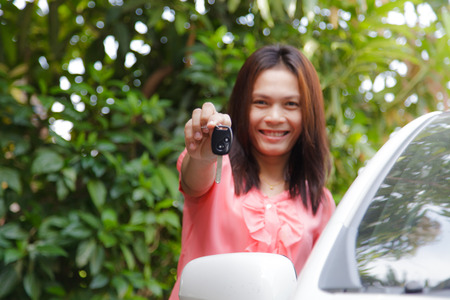 Woman holding a car key with car photo