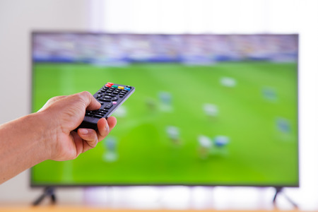 plazma: Watching tv and hand pressing remote control Stock Photo
