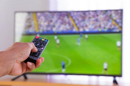 Regarder la télévision et de la main en appuyant sur la télécommande Banque d'images - 31129987
