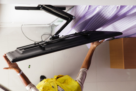 Man installing mount TV on the wall at home Stock Photo