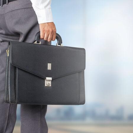 Ritagliate la vista di imprenditore in possesso di una valigetta in ufficio Archivio Fotografico