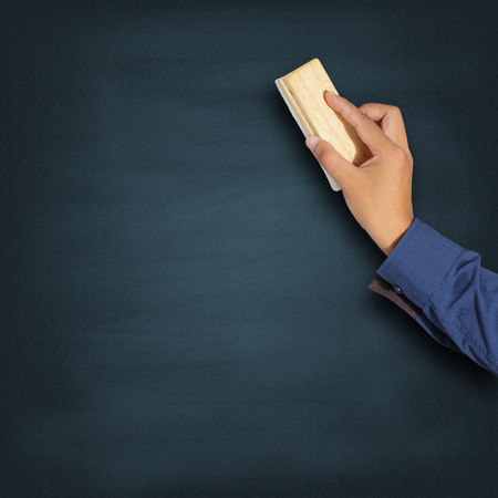 Teacher cleaning the chalkboard with a chalk duster Stock Photo