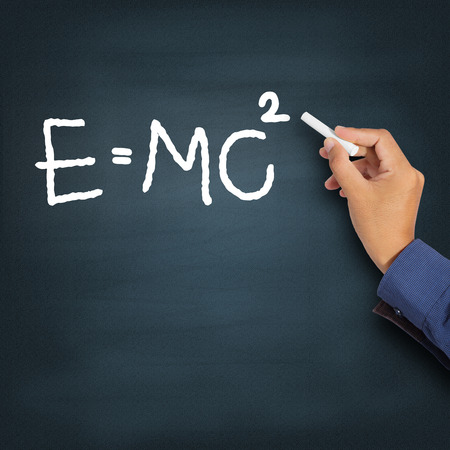 mc2: Hand writing theory of relativity (E=mc2) on a chalkboard