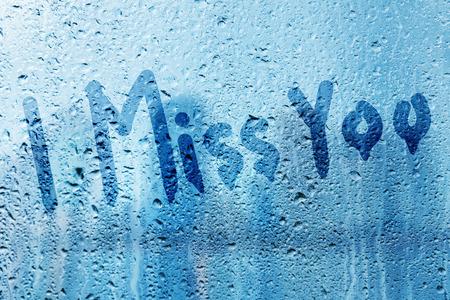 te extra�o: Lluvia sobre el vidrio con Te extra�o texto Foto de archivo