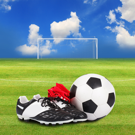 soccer shoes: Soccer ball and soccer shoes on Soccer field Stock Photo