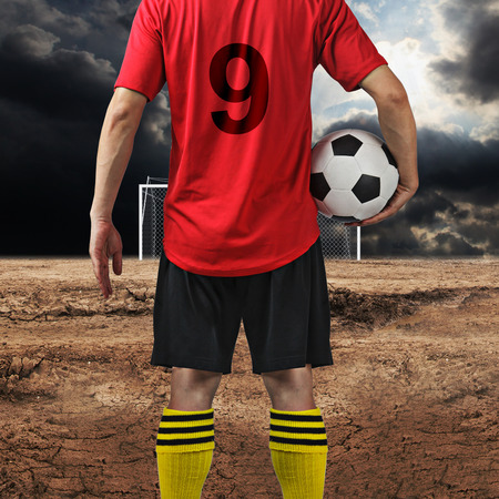 neglected: Soccer player at Neglected football field Stock Photo