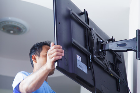 Installing mount TV on the wall at home or office Banco de Imagens