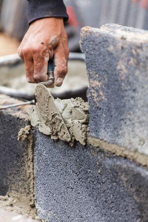 tools construction: Alba�il echando otra fila de ladrillos en el sitio
