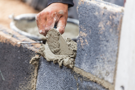 trabajando duro: Alba�il echando otra fila de ladrillos en el sitio