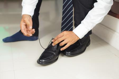 indoors: Man tying shoes indoors