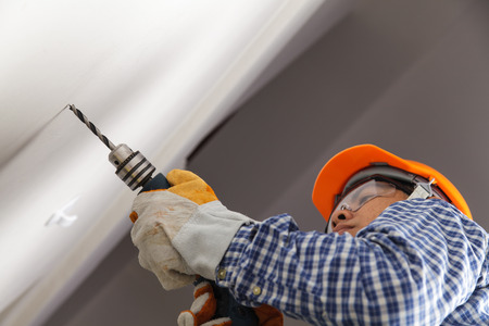 Builder or worker drilling with a machine or drill Stock Photo