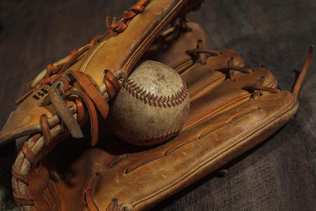 baseball game: Old baseball glove with weathered baseball on wood background Stock Photo