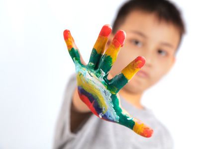 Little boy with hands painted in colorful paint on white background photo
