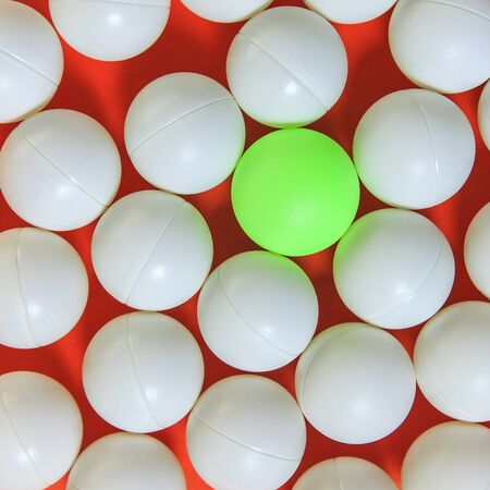 think different: Green ball and white balls, Think different concept Stock Photo