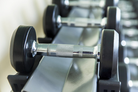 private club: Dumbbells lined up in a fitness studio, sport gym, Shot focus Stock Photo