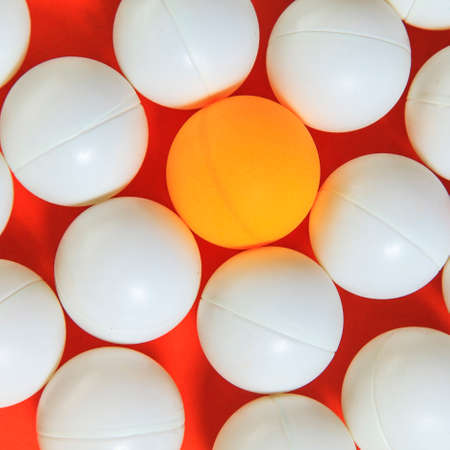 think different: Orange ball and white balls, Think different concept Stock Photo