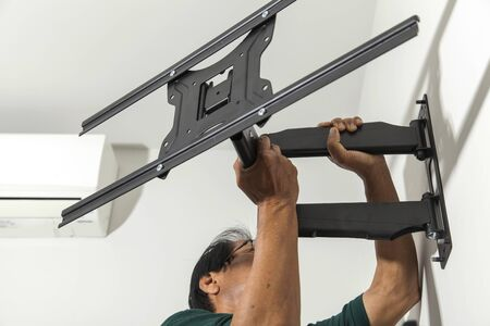 flat screen: Installing mount TV on the wall at home Stock Photo