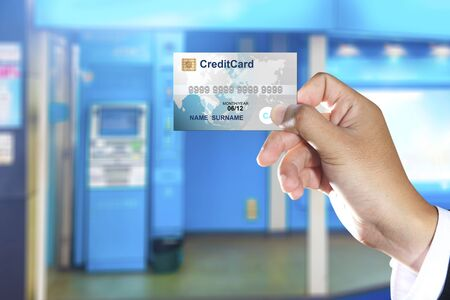 machines: Hand holding credit card with ATM machines