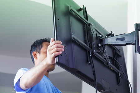 Installing mount TV on the wall at home or office Stock Photo