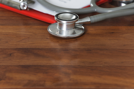 medical clipboard: Stethoscope with medical clipboard on wooden table
