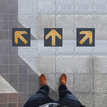 confundido: Par de zapatos de pie con tres flecha amarilla Foto de archivo