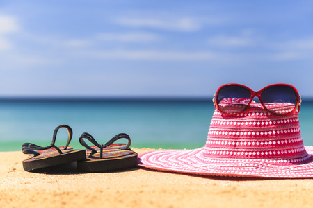pink hat: Pink hat and red glasses with flip flops on the sandy beach with blue sea and sky Stock Photo