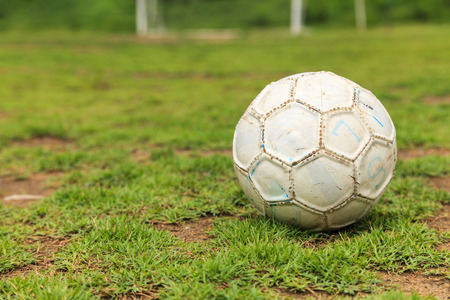 Old white soccer ball on the rough grass field