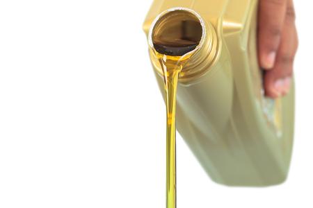 El aceite de motor de colada en el fondo blanco