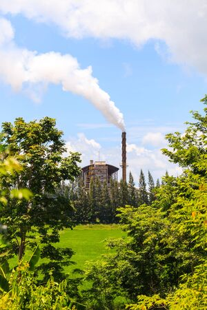 Green factory, Smoke from factory with trees and blue sky