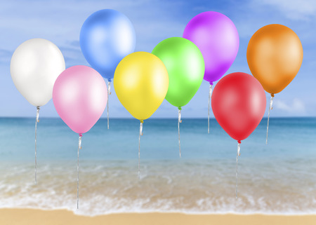 anniversary beach: Colorful balloons on beach and blue ocean with blue sky Stock Photo