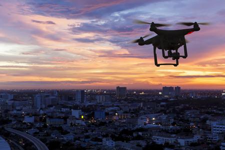 夕暮れ時市内上空を飛んでいる無人機のシルエット 写真素材