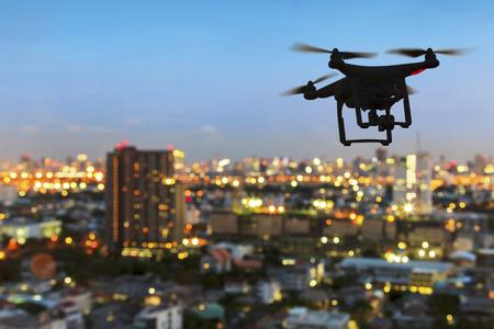Silhouette de drone volant au-dessus la ville au coucher du soleil Banque d'images - 63895652
