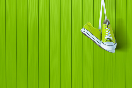 Pair of new green sneakers hanging on wooden wall Stock Photo