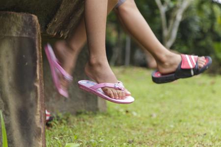 Niños sentados tienen los pies colgando en el concepto de verano de la familia, amigos