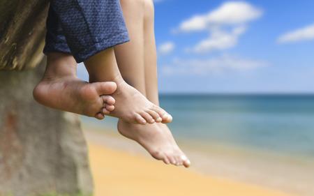 Niños descalzos piernas, Niños sentados tienen los pies colgando en el mar en el concepto de verano de la familia, los amigos
