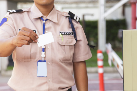 Security guard with opening barrier gate Stock Photo