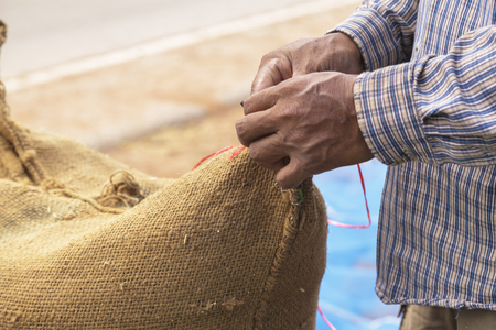 Farmer and paddy rice seed in a Burlap sack