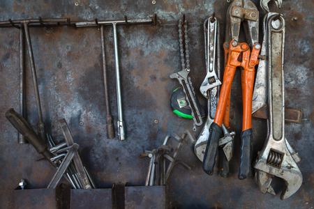 old tools: Old tools hanging on metal wall in workshop