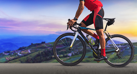 Man on a bicycle on a road between the beautiful mountains Stock Photo