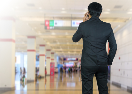 sidewalk talk: Attractive businessman using a cellphone on a modern office