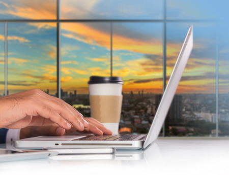 Businessman working on laptop computer at office workplace with mobile smartphone and coffee on office table
