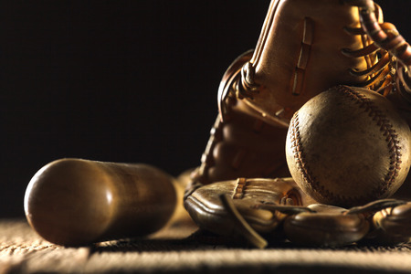 Close up image of an old used baseball, baseball bat, and baseball glove on wooden table in black background