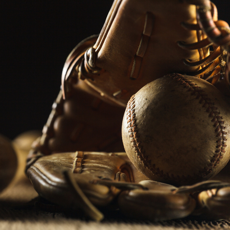 Close up image of an old used baseball and baseball glove on wooden table in black background